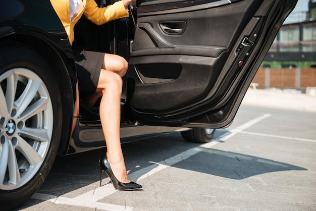 Piernas largas femeninas saliendo de su coche