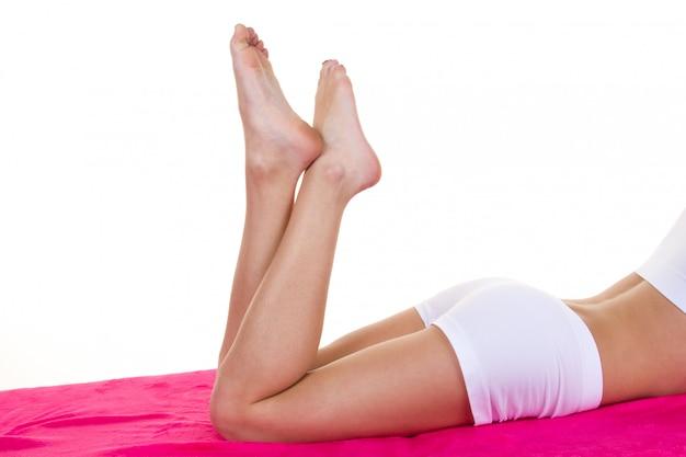 Piernas largas mujer aisladas en blanco. depilación u otro concepto de salud