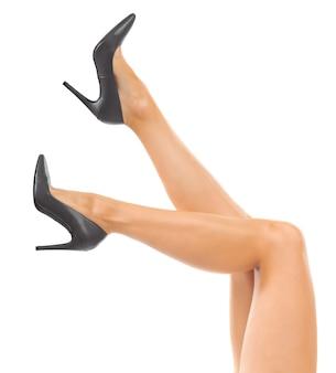 Piernas largas de mujer con zapatos negros.
