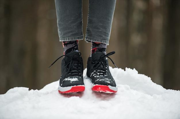 Piernas masculinas en calzado deportivo, jeans cortos y calcetines de moda de pie sobre la nieve. elegante y moderno look de invierno.