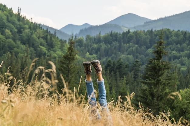 Piernas masculinas excursionista boca abajo en la ladera de la montaña