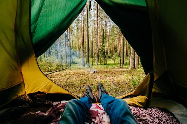 Piernas masculinas tumbado en la tienda de campaña con vistas al bosque