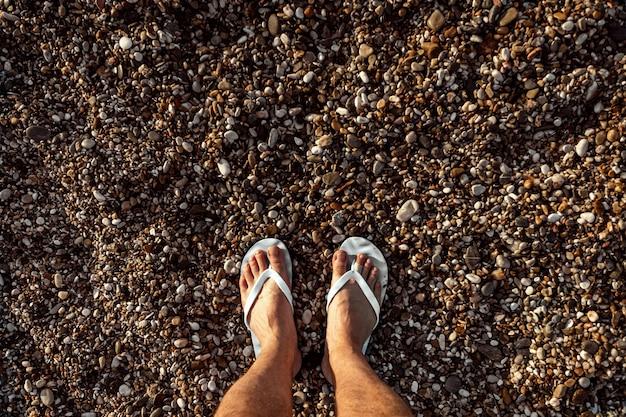 Piernas masculinas en zapatillas de playa, con un vestido de guijarros.