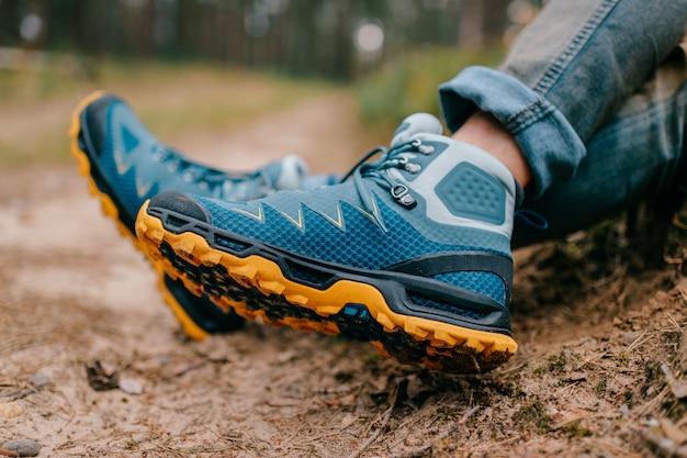 Piernas masculinas con zapatos deportivos de senderismo. piernas para hombre con botas de trekking para actividades al aire libre.