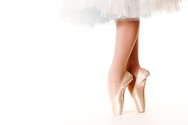 Piernas de mujer bailarina en tutú blanco y zapatos de punta sobre blanco