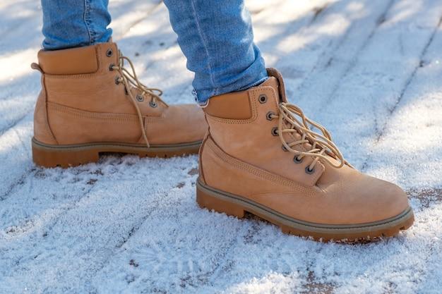 Las piernas de la mujer en las botas marrones de pie sobre la nieve.