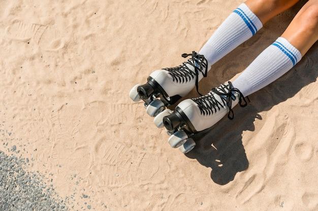 Piernas de mujer en calcetines y patines sobre arena.