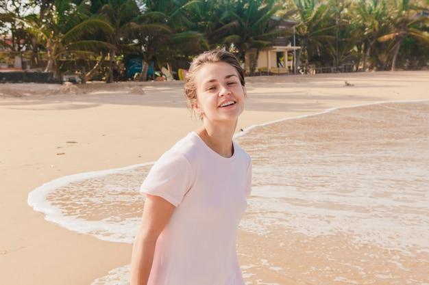 Piernas de mujer caminando por la arena de la playa