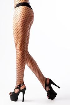 Piernas de la mujer caucásica joven en medias negras de la malla en los tacones altos en el fondo blanco.