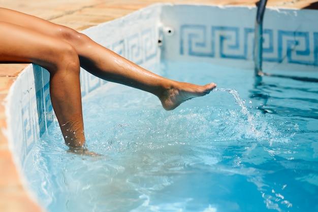 Piernas de una mujer disfrutando jugando con el agua de un spa de piscina