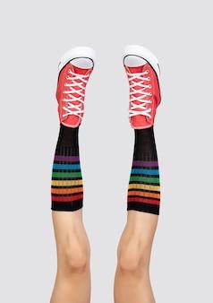 Piernas de la mujer en elegantes zapatillas rojas y calcetines de arco iris en superficie gris