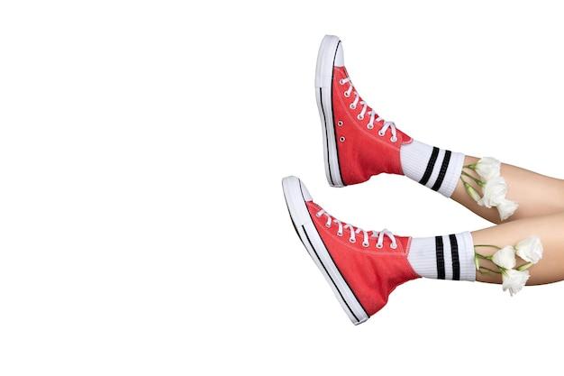 Piernas de mujer en elegantes zapatillas rojas y calcetines blancos con flores.