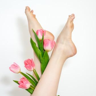 Piernas de mujer hermosa delgada suave con flores de tulipanes sobre fondo blanco