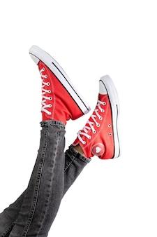 Piernas de una mujer joven en elegantes zapatillas rojas sobre superficie blanca