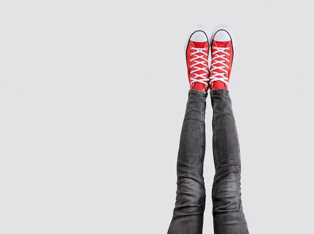 Piernas de una mujer joven en elegantes zapatillas rojas sobre superficie gris