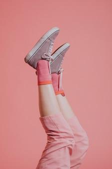 Piernas de mujer en pantalón rosa arriba en el aire.