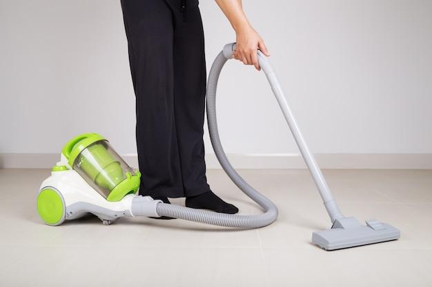 Piernas de mujer con piso de limpieza de aspiradora