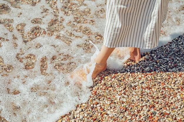 Piernas de mujer en playa de guijarros con agua de mar espumosa