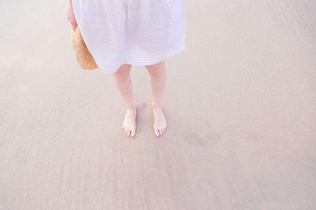 Las piernas de la mujer se relajan en un vestido blanco en una playa de arena de mar.