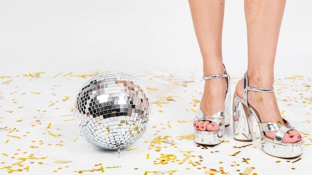 Piernas de mujer en tacones altos y bola de discoteca.