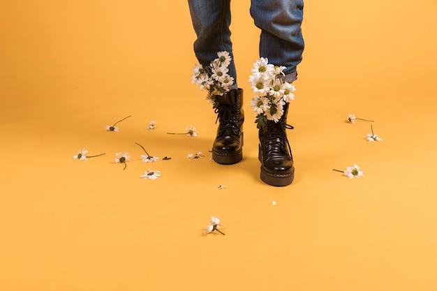 Piernas de mujer usando zapatos con flores adentro