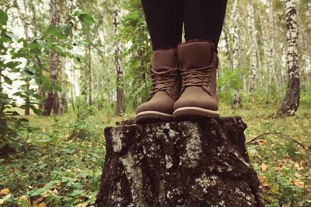 Piernas de mujer viajero en botas de cuero marrón en bosque