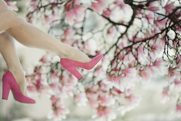 Las piernas de la mujer en los zapatos de color rosa en el árbol de magnolia en flor