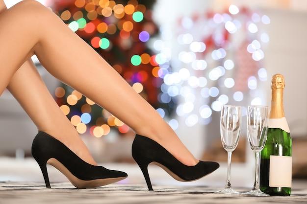 Piernas de mujer en zapatos de tacones y champán en casa