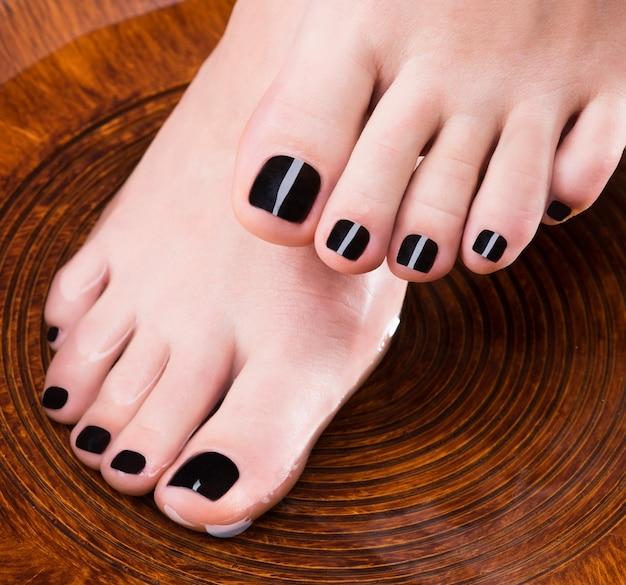 Piernas de mujeres hermosas con pedicura negra después de procedimientos de spa - concepto de tratamiento de spa
