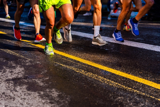 Piernas musculosas de un grupo de varios corredores entrenando corriendo sobre asfalto