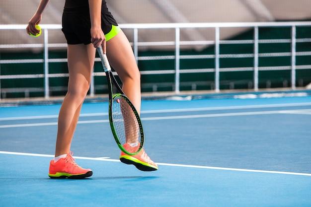 Piernas de niña en una cancha de tenis cerrada con pelota y raqueta