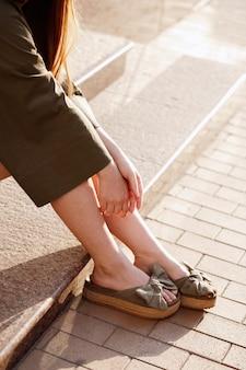 Las piernas de la niña de cerca en sandalias verdes