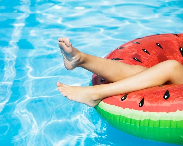 Piernas de niña en flotador en la piscina