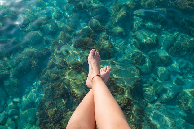Piernas de niña de ibiza en el agua clara de la playa de portinatx