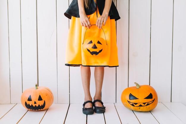 Piernas de niña sosteniendo la cesta de halloween con calabazas en los lados