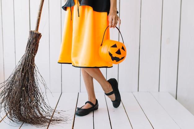 Piernas de niña sosteniendo cesta de halloween y escoba