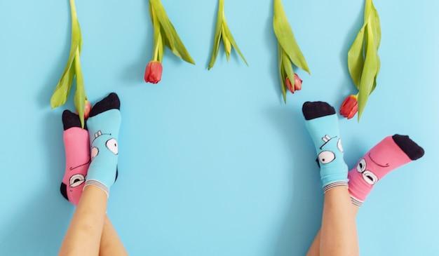 Piernas de los niños en divertidos calcetines levantados sobre un fondo azul, pies divirtiéndose, concepto creativo