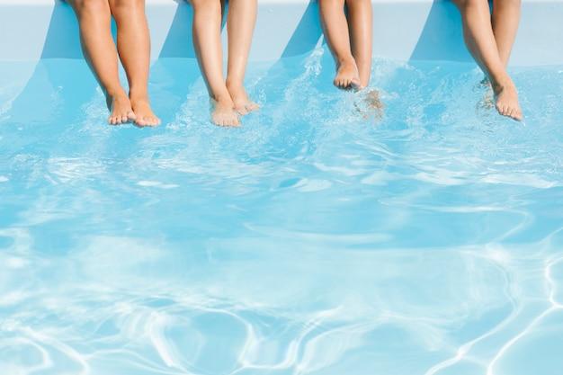 Piernas de niños sobre agua cristalina