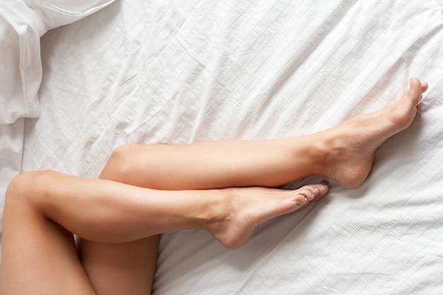 Piernas perfectas y hermosas de la mujer en cama