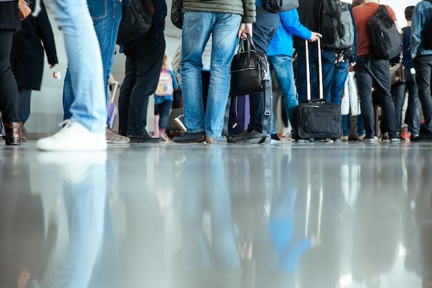 Piernas pies soporte aterrizaje portón maletas equipaje gente aeropuerto terminal viaje salida hombre inferior muchas reflexiones piso