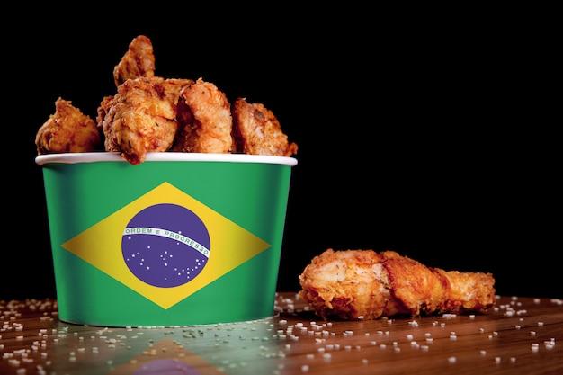 Piernas de pollo a la barbacoa en la bandera del cubo de brasil