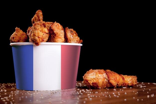 Piernas de pollo a la barbacoa en un cubo blanco