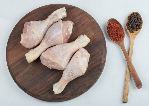 Piernas de pollo fresco crudo con dos pimientos de cuchara sobre fondo blanco.