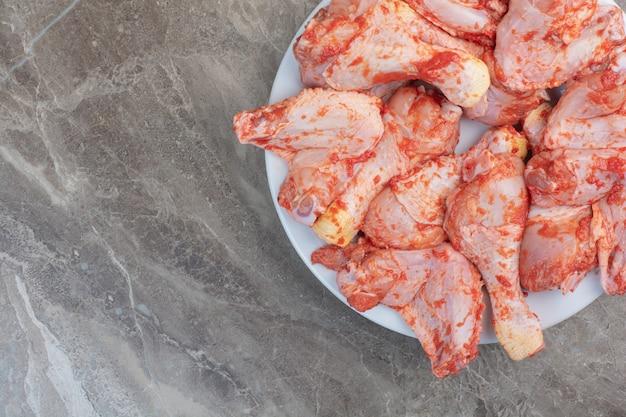 Piernas de pollo sin preparar con especias en la placa blanca.