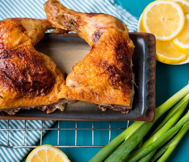 Piernas de pollo de primer plano con rodajas de limón y cebolla verde