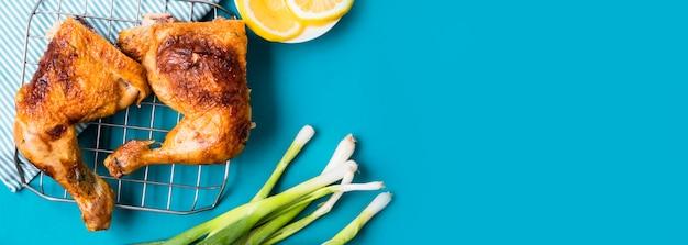Piernas de pollo vista frontal con rodajas de limón y cebolla verde con espacio de copia
