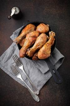 Piernas puntiagudas de pollo frito en una sartén de hierro fundido sobre un fondo de piedra o hormigón oscuro