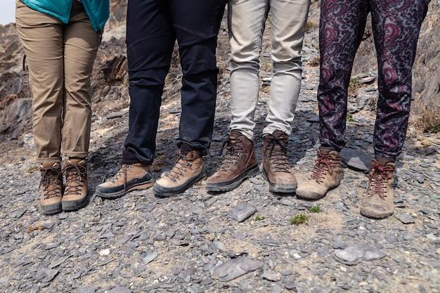 Piernas turísticas juntas en botas de trekking marrones con cordones en acantilado rocoso