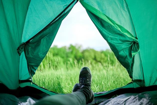 Piernas del viajero en botas de montaña en una carpa al aire libre