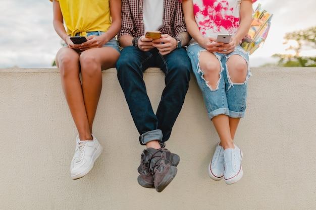 Piernas en zapatillas de deporte de la joven compañía de amigos sentado en el parque con teléfonos inteligentes